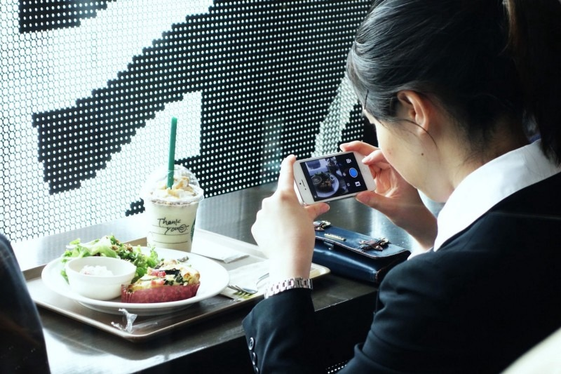 Japanese woman taking picture of food to social media